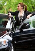 Woman at car door — Stock Photo