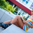 Teen girl wearing rollerskates with book  — Stock Photo