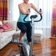 Woman on stationary bicycle — Stockfoto