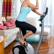 Woman on stationary bicycle — Stock Photo #20349387