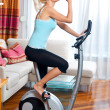 Woman on stationary bicycle — Stok fotoğraf