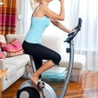 Woman on stationary bicycle — Stock Photo #20349425