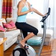 Woman on stationary bicycle — Stock Photo