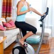 Woman on stationary bicycle — ストック写真