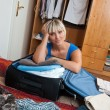 Stock Photo: Woman packing clothes