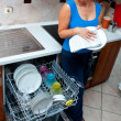 Attractive woman washing dishes — Stockfoto