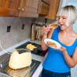 Attractive woman eating toast — Stock Photo