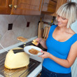 Attractive woman using toaster — Stock Photo