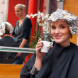 Woman relaxing over coffee in hair salon - Stock Photo