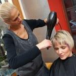 Stylist drying woman hair — Stock Photo #20447965