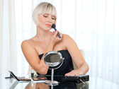 Attractive woman putting make up — Stock Photo