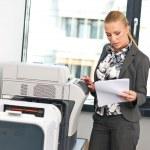 Woman working on copy machine — Stock Photo #20463235