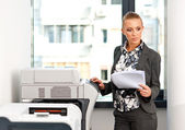 Woman working on copy machine — Stock Photo