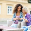 Two teen woman friends having fun sitting in outdoor cafe — Stock Photo #21415643