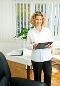 Attractive adult woman in her office — Stock Photo