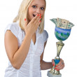 Woman with trophy full of money — Stockfoto