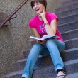 Girl with book on the stairs — Stockfoto