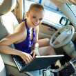 Woman with laptop in the car — Stockfoto #22202587