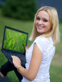 Woman with laptop outside — Stock Photo