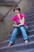 Girl with book on the stairs — Stock Photo