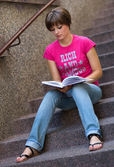 Teen girl with book on the stairs — Stock Photo