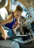Woman with laptop in the car — Stock Photo