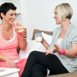 Two mature woman friends chating over coffee - Stock Photo