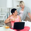 Two mature woman friends with laptop at home — Stock Photo
