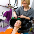 Hair stylist washing woman hair — Stock Photo