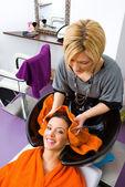 Hair stylist washing woman head — Stock Photo