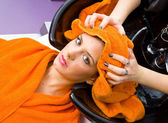 Hair stylist washing woman head — Stock Photo