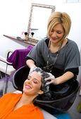 Hair stylist washing woman hair — Stock Photo