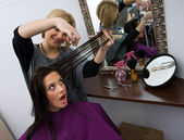 Hair stylist cuting woman hair — Stock Photo