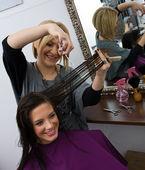 Hair stylist cuting woman hair — Stock Photo