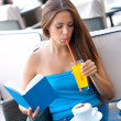Woman reading book in coffee shop — Foto Stock