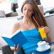 Woman reading book in coffee shop — Stockfoto
