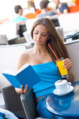 Woman reading book in coffee shop — Stock Photo