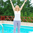 Mature woman relaxed in front of the pool — Stock Photo