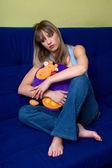 Teen flicka i soffan kramar kudden — Stockfoto