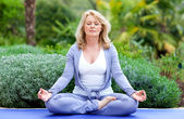 Mature woman in yoga position — Stok fotoğraf