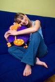 Teen girl on the sofa hugging pillow — Stock Photo
