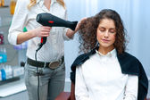 Stylist drying woman hair in salon — Stock Photo