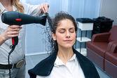 Stylist drying woman hair in salon — Stock Photo