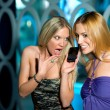 Two girl friends talking to mobile phone — Stock Photo