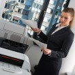 图库照片: Business womnext to office printer