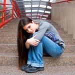 Sad teen girl on school stairs — Stock Photo #25982453