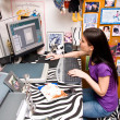 Stock Photo: Teen girl in messy room on computer