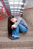 Sad teen girl on school stairs — Stock Photo