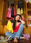 Confused girl in front of open closet — Stock Photo