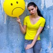 Teen girl with sad smiley balloon — Stock fotografie